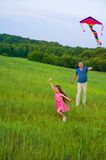 Girl flying the kite in the field. Royalty Free Stock Photography