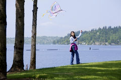 Girl flying kite by the lake Stock Photo