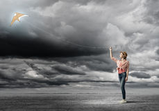 Girl and flying kite Royalty Free Stock Images