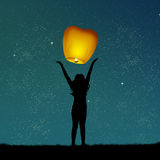 Girl with flying lanterns Stock Image