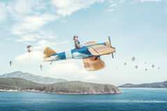 Girl flying old plane . Mixed media Royalty Free Stock Image