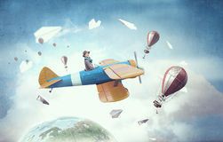 Girl flying old plane . Mixed media Royalty Free Stock Images
