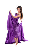 Girl in flying purple silk dress Stock Image