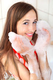 Girl with foam on hands. Young happy girl with foam on hands in bathroom stock photos