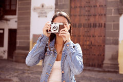 Girl focusing on taking a picture. Pretty young girl focusing on taking a picture with her camera, her hair loose wearing casual clothing in front of a steel Stock Photos