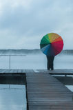 Girl in the fog on the pier with a rainbow umbrella looking into the distance, view from the back Stock Photography