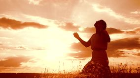 Girl folded her hands in prayer silhouette at sunset. woman praying on her knees. slow motion video. concept
