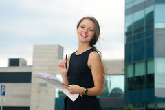 Girl with a folder for papers in her hands cheerfully laughs Royalty Free Stock Photography