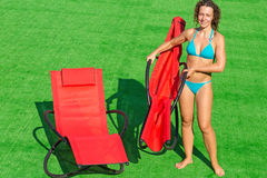 Girl folding deck-chair on green field Stock Photography