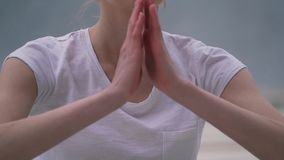 The girl folds her hands for meditation stock footage