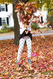 Girl and Folige. A girl is shrowing the foliage leaves in the air Royalty Free Stock Photos