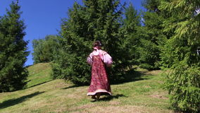 Girl in folk costume dancing on the grass stock video footage