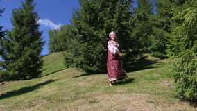 Girl in folk costume dancing on the grass stock footage