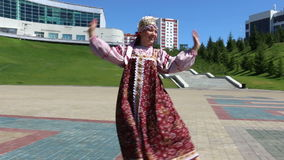 Girl in folk costume dancing on the square stock video