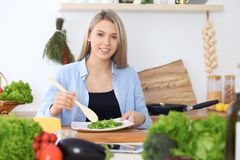 Girl following recipe on digital tablet while cooking in kitchen. Healthy meal and culinary concept Stock Photos