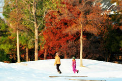 Girl Follows Teen Woman on Snowy Hill Stock Images