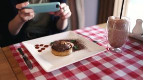 A girl food blogger takes pictures of her dessert nut tart with chocolate ganache and banana sitting in a cafe.