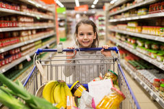 Girl with food in shopping cart at grocery store. Sale, consumerism and people concept - happy little girl with food in shopping cart at grocery store Royalty Free Stock Photography
