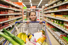 Girl with food in shopping cart at grocery store. Sale, consumerism and people concept - happy little girl with food in shopping cart at grocery store Stock Photography