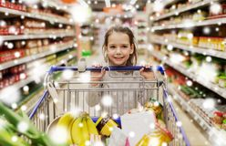 Girl with food in shopping cart at grocery store. Sale, consumerism and people concept - happy little girl with food in shopping cart at grocery store or Stock Photo