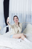 Girl fooling around and showing tongue and taking selfie on smartphone Royalty Free Stock Photos