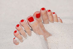Girl foot. In sand on the beach - red nails stock photos