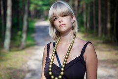 Girl in the forest. Girl standing in the forest with big collar on her neck Royalty Free Stock Photo