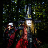 Girl in the forest dressed Halloween witch costume. Holiday concept stock image