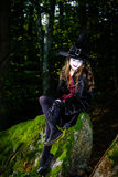 Girl in the forest dressed Halloween witch costume Stock Image