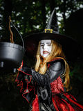 Girl in the forest dressed Halloween witch costume Stock Photo