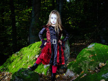 Girl in the forest dressed Halloween witch costume. Holiday concept stock photography