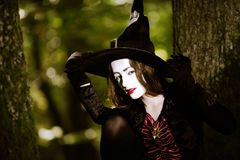 Girl in the forest dressed Halloween witch costume Royalty Free Stock Photo