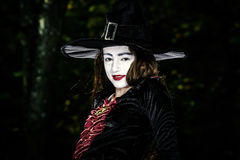 Girl in the forest dressed Halloween witch costume Royalty Free Stock Images