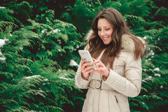 Girl in forest holding phone. Smiling girl in forest using mobile phone Stock Photos