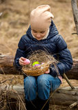 Girl in forest looking at colored Easter eggs in basket Stock Image