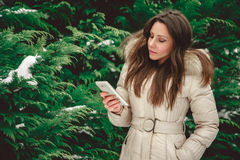 Girl in forest looking at phone seriously. Girl in green snowy forest looking at mobile phone seriously Royalty Free Stock Photos