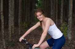 Girl in forest with mountain bike Stock Photo