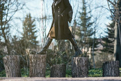 The girl in the forest steps over from the stump to the stump. Royalty Free Stock Photo