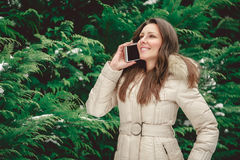 Girl in forest talking on the phone. Smiling girl in forest talking on the mobile phone Royalty Free Stock Image