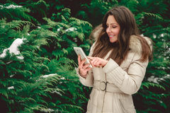 Girl in forest touching phone. Girl in green snowy forest touching phone Stock Photos