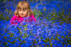 Girl among forget-me-nots flowers Royalty Free Stock Images