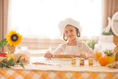 Girl in the form of a cook rolls out the dough Stock Image