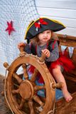 Girl in the form of pirates at the helm. royalty free stock photo