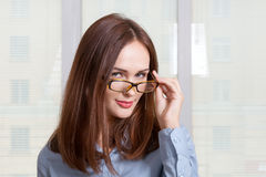 Girl in formal attire looking over his glasses Royalty Free Stock Images