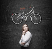 A girl in formal clothes is dreaming about a new bicycle. A sketch of a bicycle is drawn on the black chalkboard. Stock Photo
