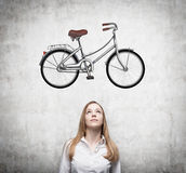 A girl in formal clothes is dreaming about a new bicycle. A sketch of a bicycle is drawn on the concrete wall. Royalty Free Stock Photos
