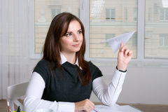 Girl in formal clothes holding a paper airplane Royalty Free Stock Photo