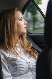 Girl in formal clothes rides in a car stock photo