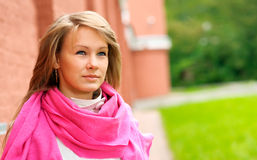 Girl at fortification. Young beautiful woman with pink scarf costs at an ancient wall Royalty Free Stock Images