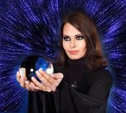 Girl with fortune telling ball against  star sky. Stock Photos